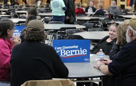 Iowa caucus-goers sit at a table marked with a Bernie Sanders poster