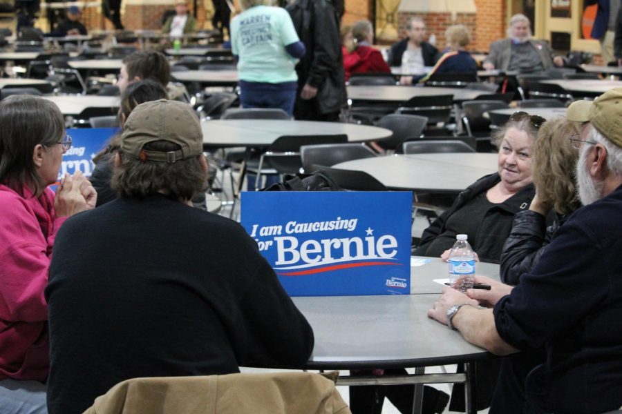 Iowa+caucus-goers+sit+at+a+table+marked+with+a+Bernie+Sanders+poster